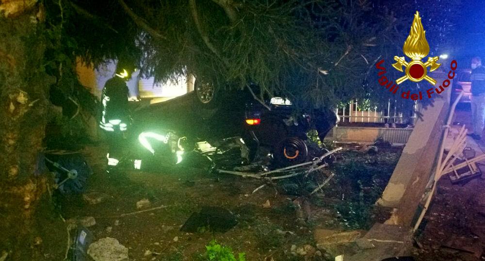 Auto sfonda una recinzione e si capotta nel cortile, due feriti
